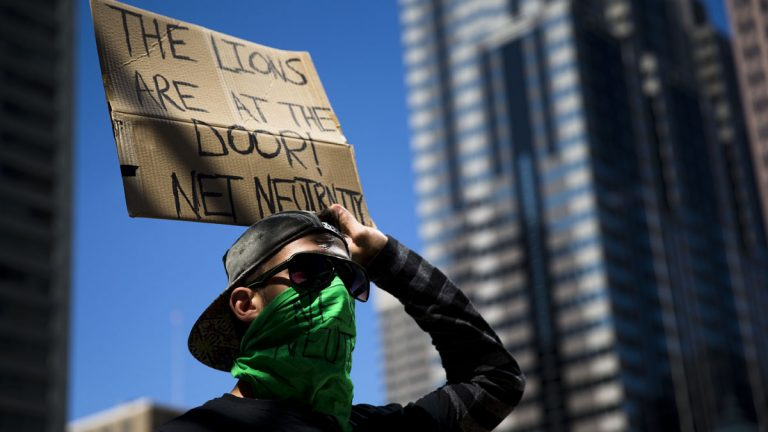 A protester demonstrates across the street from the Comcast Center in Philadelphia in September. At a  similar demonstration Thursday night, protesters called for further Federal Communications Commission regulation of Internet traffic to support 'net neutrality.' (AP Photo/Matt Rourke)