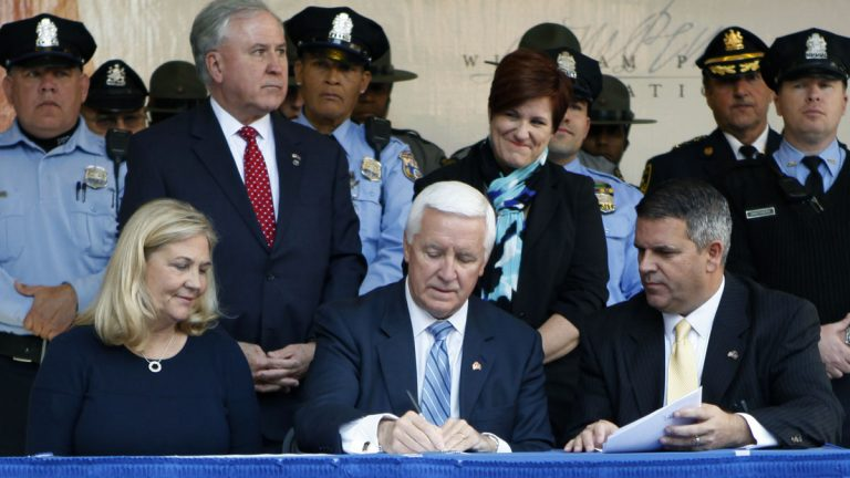 Gov. Tom Corbett, center, signs the law last month as Maureen Faulkner, widow of police Officer Daniel Faulkner, and Pa. state Rep. Mike Vereb look on. Tuesday Oct. 21, 2014 in Philadelphia. Corbett said the measure was intended to curb the