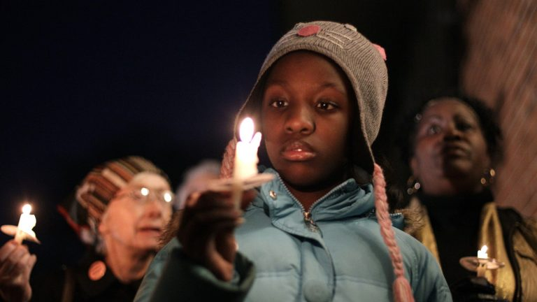 In January of 2012, Courtney Thornton looks at her candle during a vigil outside the Chester Upland School District administration building in Chester, Pennsylvania. More than two decades after being declared financially distressed, the long-struggling district may not be able to open its doors this school year with a