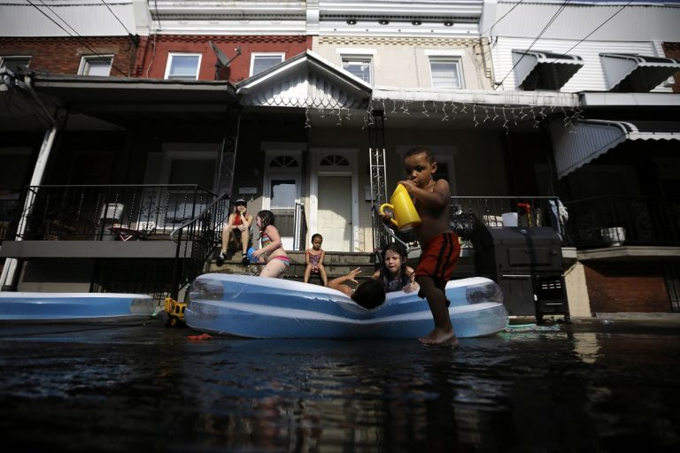 Jayden Jones, from right, 2, Veronica Caines, 6, Aliyah Nguyen, 5, Kianna Roman, 4, and Juliann Esola, 5, cool off in a wade pool under the watch of Amber Escola, of Philadelphia (AP File Photo/Matt Slocum)