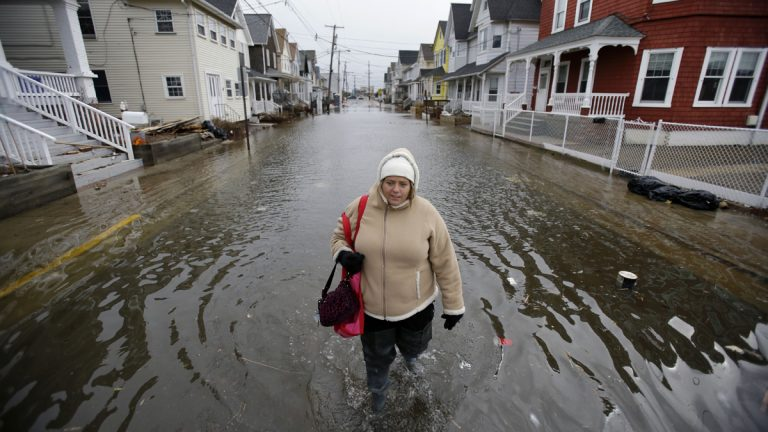 Carol Marelli walks down her flooded street in March 2013, in Sea Bright, New Jersey, after an overnight storm. A new national poll finds that 70 percent of those surveyed believe climate change is an important issue that is affecting areas beyond the coast. (AP file photo)