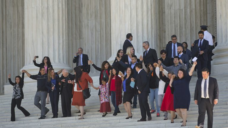 Supporters of  immigration reform hold hands as they leave together after hearing arguments at the Supreme Court in the case U.S. versus Texas Monday in Washington. (AP Photo/Pablo Martinez Monsivais)