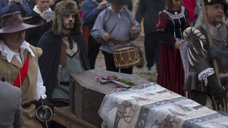 A coffin is wheeled though a street market during a mock funeral for Spanish writer Miguel de Cervantes