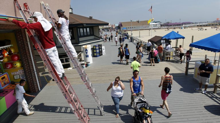 Workers put the finishing touches on fresh paint at an arcade on the boardwalk early Friday in Point Pleasant Beach