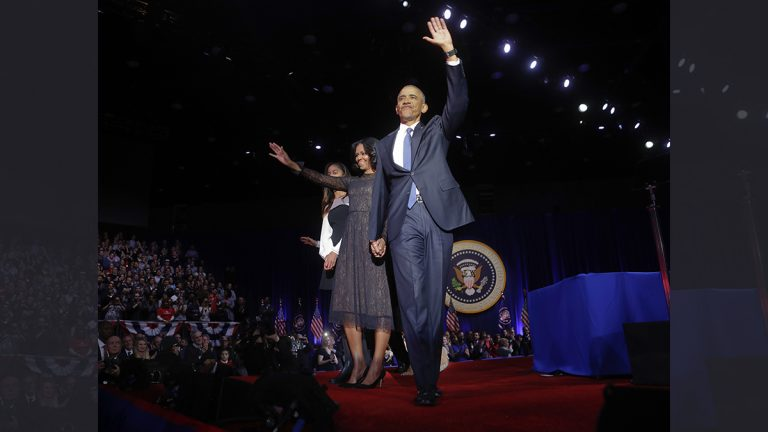 President Barack Obama waves on stage with first lady Michelle Obama
