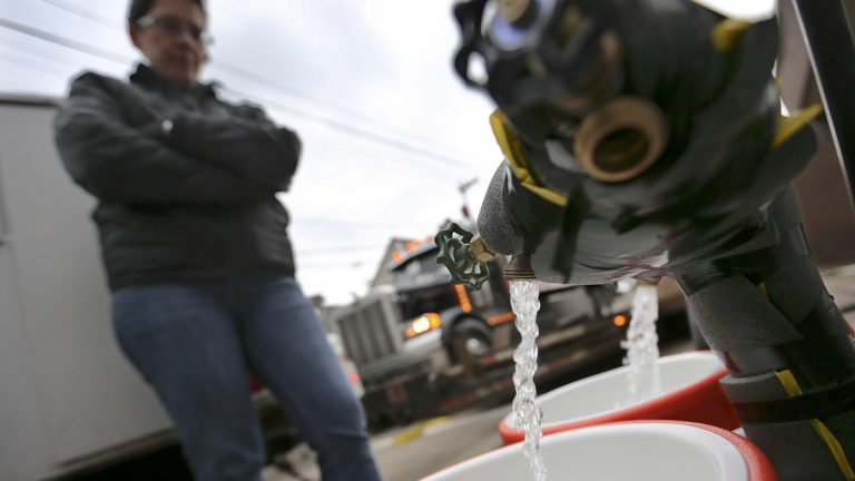 Ronette Cooley fills water containers at a fire station in Pittsburgh's Lawrenceville neighborhood. The City of Pittsburgh set up 15 water stations across the city to provide residents under a flush and boil advisory with potable water. Lower than normal levels of chlorine were found at a city reservoir that supplies water to much of the central and eastern parts of the city. (AP Photo/Keith Srakocic)