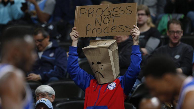 A Philadelphia 76ers fan wears a bag over his head and holds up a placard while watching his team face the Denver Nuggets in the first half of an NBA basketball game Wednesday