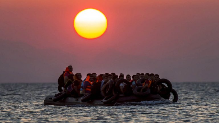 Migrants on a dinghy arrive at the southeastern island of Kos, Greece, after crossing from Turkey in August. While New Jersey Gov. Chris Christie adamantly opposes allowing Syrian refugees to resettle in the Garden State, residents are evenly divided.  (AP file photo)
