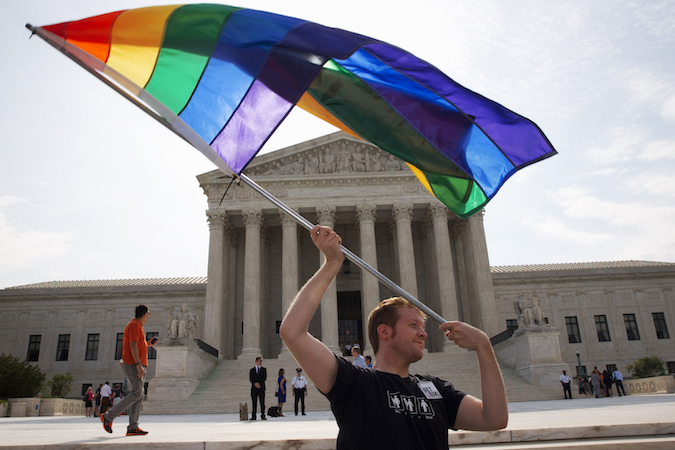 John Becker, 30, of Silver Spring, Md., waves a rainbow flag in support of gay marriage outside of the Supreme Court in Washington. (AP Photo/Jacquelyn Martin)