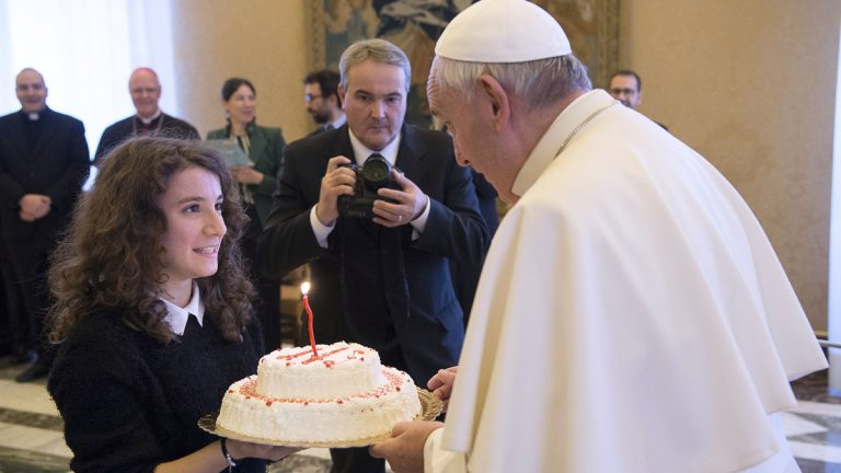 Pope Francis blows a candle on a birthday cake he was presented by a group of youths of the Catholic Action he received during a private audience at the Vatican Thursday. Pope Francis entered his 80th year on Thursday amid hopes among his critics that it will be his last — at least as pope. (L'Osservatore Romano/pool photo via AP)