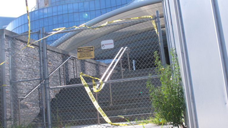 Weeds and caution tape line the entrance to the former Revel casino in Atlantic City, N.J. Friday Aug. 21, 2015. Three windows are missing or smashed at the casino, which has been vacant nearly a year. (AP Photo/Wayne Parry)