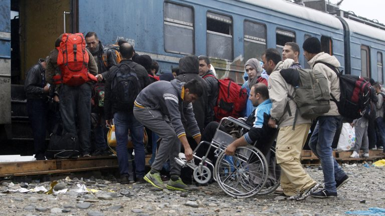 People help a wheelchair user board a train with others, heading toward Serbia, at the transit camp for refugees near the southern Macedonian town of Gevgelija early this month. Several thousand migrants and refugees enter daily from Greece into Macedonia on their way through the Balkans toward the more prosperous European Union countries. More than 500,000 people have arrived this year in EU seeking sanctuary or jobs, sparking the EU's biggest refugee emergency in decades. (Boris Grdanoski/AP Photo)