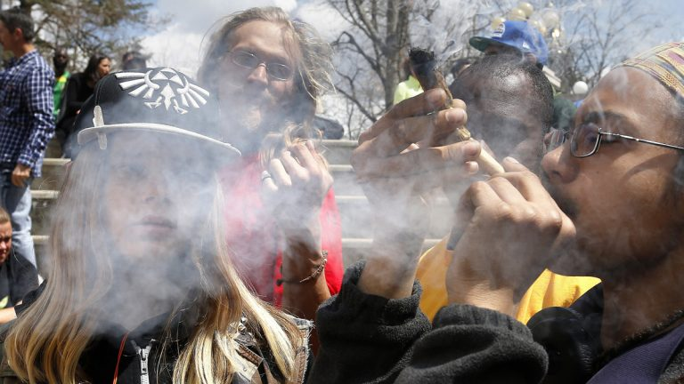 Young party-goers listen to music and smoke marijuana during the annual 4/20 marijuana festival in Denver's downtown Civic Center Park. A new study suggests that long-term marijuana users who smoke several times a week are more likely to suffer from financial and relationship problems than their peers.(AP file photo)