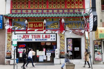 People walk past the Joy Tsin Lau restaurant in the Chinatown neighborhood of Philadelphia. A 'food source' was the root of a food poisoning outbreak that sickened dozens of restaurant patrons in February. (AP file photo)
