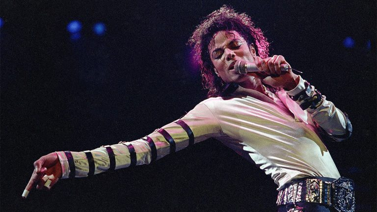 In this Feb. 24, 1988 file photo, Michael Jackson leans, points and sings, dances and struts during the opening performance of his 13-city U.S. tour, in Kansas City, Mo. (AP Photo/Cliff Schiappa, File)