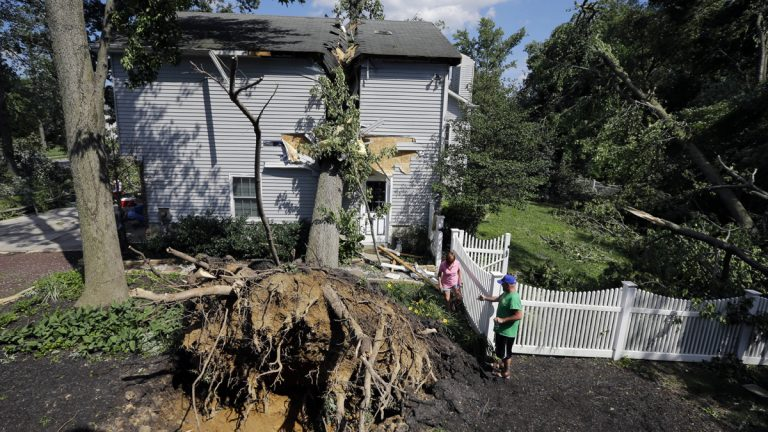 Joe Higgins, right, helps Debbie Epifano walk past a large tree that crashed through their home during a storm Tuesday night in Gibbstown, New Jersey on June 24. The home sustained major structural damage, but no one was injured. Atlantic, Burlington, Camden and Gloucester counties were declared disaster areas Wednesday by the U.S. because of the storm damage. (AP Photo/Mel Evans