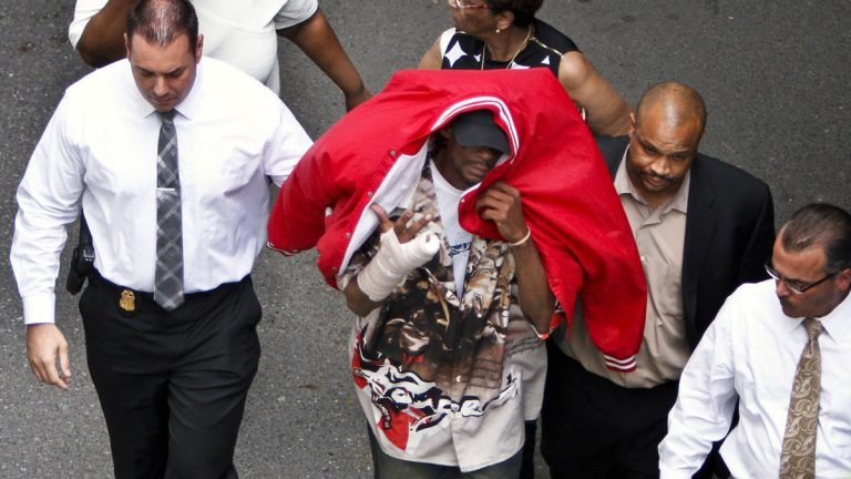 Sean Benschop, center, with red jacket over his head, walks with investigators to the Philadelphia Police Department's Central Detectives Division in 2013.Benschop's attorney says he will plead guilty Tuesday to charges including involuntary manslaughter and causing a catastrophe. (AP file photo)