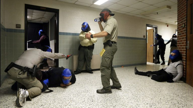 FBI instructor Mike Sotka, center, films  police officers in 2013 as they participate in an active shooter drill in a college classroom building in Salisbury, Maryland, as part of an FBI program that teaches local law enforcement best practices for responding to mass shootings. (Patrick Semansky/AP Photo)