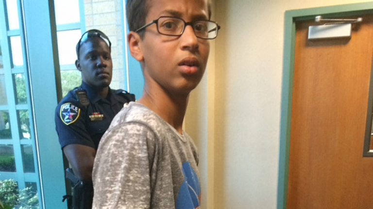 In this Sept. 14, 2015 photo provided by Eyman Mohamed, her brother Ahmed Mohamed stands in handcuffs at Irving police department in Irving, Texas. The 14-year-old Muslim boy became a sensation on social media Wednesday, Sept. 16 and got an invitation to the White House after word spread that he had been placed in handcuffs and suspended for coming to class with a homemade clock that school officials thought resembled a bomb. (Eyman Mohamed via AP)