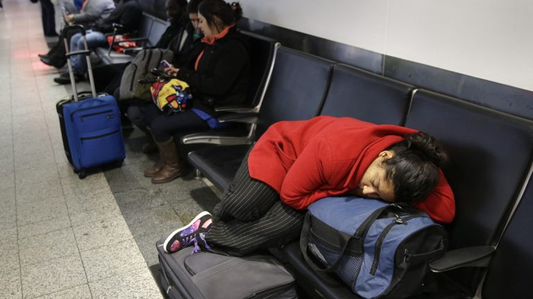A woman sleeps on top of her luggage at LaGuardia Airport in New York