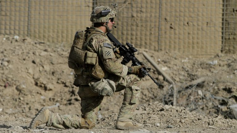 An American soldier, part of the NATO-led International Security Assistance Force (ISAF), kneels down at the site of a suicide attack in Wardak Province, east of Kabul, Afghanistan, Sunday, Sept. 8, 2013. Taliban militants detonated a car bomb outside an Afghan intelligence office near the capital Sunday and then tried to attack it on foot with guns, officials and the insurgent group said. At least four soldiers guarding the compound were killed and six insurgents died in the assault, officials said. (Ahmad Jamshid/AP Photo)