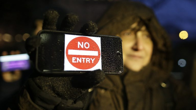 A demonstrator stands outside the Apple store on Fifth Avenue