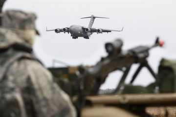 An Army guard looks on as an Air Force C-17 cargo plane lands at Joint Base McGuire Dix Lakehurst in New Jersey. (Mel Evans/AP file photo)