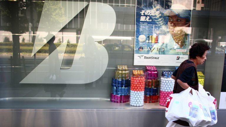 A shopper strolls by Bridgestone's head office in Tokyo (Junji Kurokawa/AP Photo)