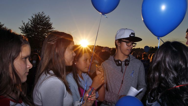 Students hold candles and balloons as they join hundreds of people gathering in the setting sun, for an anti-bullying rally Sunday, Oct. 12, 2014, in Sayreville, N.J. Organizers say the goal of the event is to promote unity and healing within the community, as well as to show support for the victims of bullying. (Mel Evans/AP Photo)