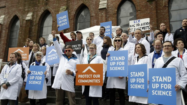 Scientists hold signs during a rally in conjunction with the American Geophysical Union's fall meeting Tuesday