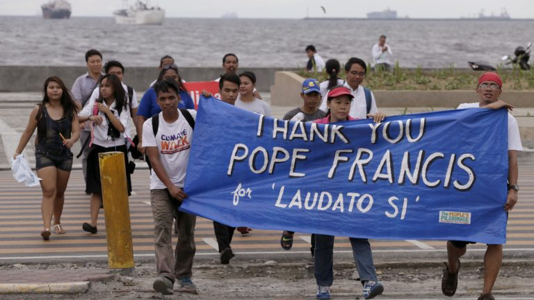 Environmental activists carry a banner as they march toward a Roman Catholic church to coincide with Pope Francis' encyclical on climate change Thursday in Manila, Philippines. In a high-level, 190-page document released Thursday, Pope Francis  describes ongoing human damage to nature as 'one small sign of the ethical, cultural and spiritual crisis of modernity.' (Bullit Marquez/AP Photo)