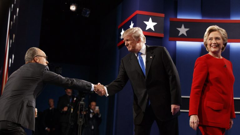Republican presidential candidate Donald Trump (center) shakes hands with moderator Lester Holt (left) as Democratic presidential candidate Hillary Clinton walks to her lectern during the first presidential debate at Hofstra University