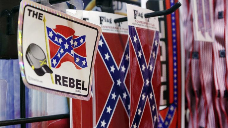 Small Confederate flags are displayed on a shelf at Arkansas Flag and Banner in Little Rock