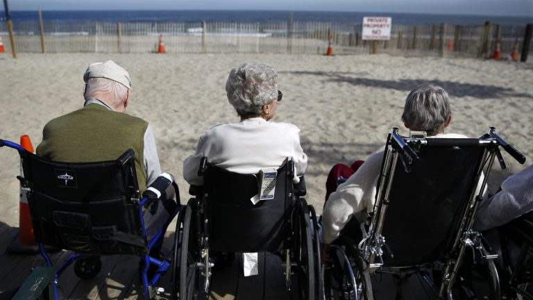 Elderly people from a nearby senior citizen facility sit on the edge of the boardwalk and look out over the ocean on the first day of autumn Tuesday