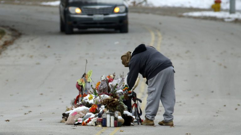 A woman looks at a memorial in the middle of the street Monday