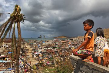 Filipino children play as houses damaged by Typhoon Haiyan are seen in the background in Marabut, Philippines, Thursday, Nov. 14, 2013. (Dita Alangkara/AP Photo, file)