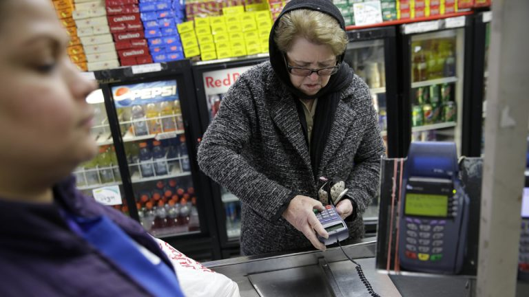 A woman pays for her groceries using a food stamp program at a supermarket  (Seth Wenig/AP Photo)