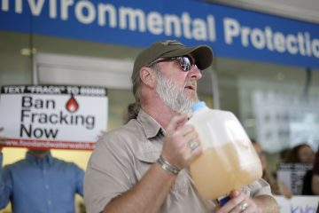 Ray Kemble of Dimock, displays a jug of what he identifies as his contaminated well water in this August 2013 file photo (Matt Rourke/AP Photo)