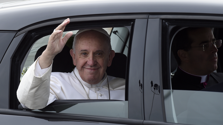Pope Francis waves from inside his car after arriving at Philadelphia International Airport in Philadelphia, Saturday, Sept. 26, 2015. The Pope will spend the last two of his six days in the U.S. in Philadelphia as the star attraction at the World Meeting of Families, a conference for more than 18,000 people from around the world that has been underway as the pope traveled to Washington and New York. (Susan Walsh/AP Photo)