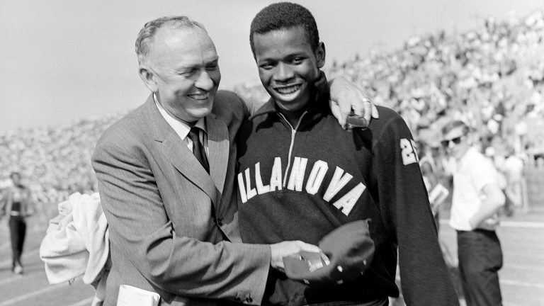 In this June 24, 1961, file photo, Villanova sprinter Frank Budd (right) is congratulated by coach James Elliott after winning the 100-yard dash at the National AAU track and field championships in New York, with a world record time of 9.2 seconds. Budd, an Olympic sprinter and former 100-meter dash world record holder, died Tuesday, April 29, 2014, Villanova University said. He was 74. (AP Photo/File)