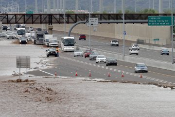 This Aug. 19, 2014 file photo shows flash flood waters from the overrun Skunk Creek flood I-10 in northwestern Phoenix. Global warming is here, human-caused and can already be considered dangerous, a draft of a new international science report says, warning that it is increasingly likely that climate change could be irreversible. The United Nations' Intergovernmental Panel on Climate Change on Monday sent governments a final draft of its synthesis report, which combines three earlier, gigantic documents by the Nobel Prize-winning group. There is little in the report, that wasn't in the other more-detailed versions, but the language is more stark and the report attempts to paint a bigger picture of the problem caused by the burning of fossil fuels, such as coal, oil and gas. (Matt York/AP Photo, file)