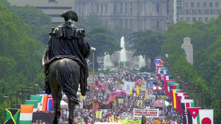 Overlooked by a statue of George Washington on a horse, protesters march up Ben Franklin Blvd., toward the Philadelphia Museum of Art, Sunday, July 30, 2000, on the eve before the Republican National Convention. (William Wilson Lewis III/AP Photo)