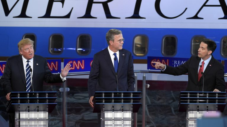 Republican presidential candidates businessman Donald Trump, (left), and Scott Walker, (right), both speak as Jeb Bush, listens during the CNN Republican presidential debate at the Ronald Reagan Presidential Library and Museum on Wednesday, Sept. 16, 2015, in Simi Valley, Calif. (Mark J. Terrill/AP Photo)