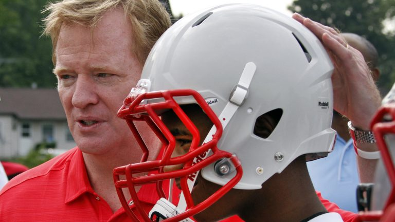 In this 2012 photo, NFL commissioner Roger Goodell, left, poses with a youth football player from a low income family who are among thousands nationwide to benefit from a youth safety and helmet replacement program, partially sponsored by the NFL. (Gene J. Puskar/AP Photo, file)