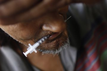 A heroin addict holds a used syringe in his mouth after shooting up. (Brennan Linsley/AP file photo)