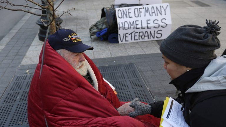 In this November 2013 photo, homeless Korean War veteran Thomas Moore, 79, left, speaks with Boston Health Care for the Homeless street team outreach coordinator Romeena Lee on a sidewalk in Boston. Moore said he accidentally killed his best friend with a phosphorous grenade during one firefight and spent months afterward at Walter Reed Army Medical Center in Washington. (Steven Senne/AP Photo)