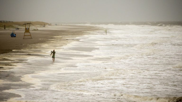 A surfer walks the beach while looking for waves from the surge of Hurricane Hermine