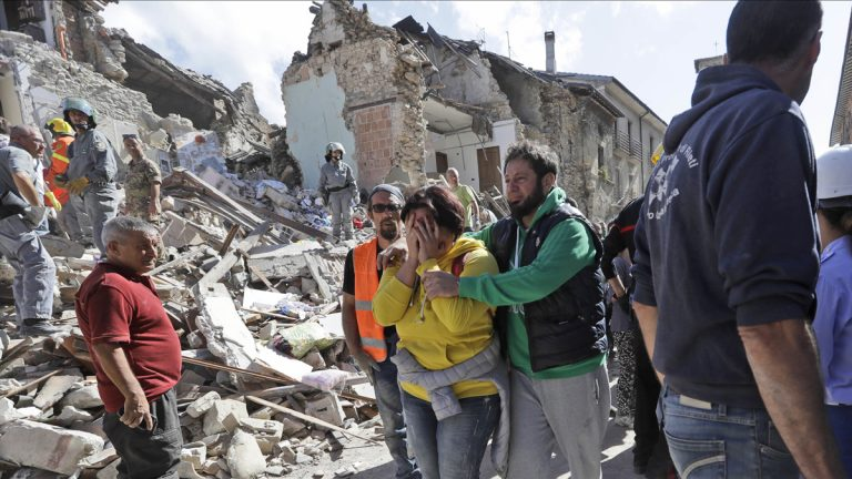 A woman is comforted as she walks through rubble after an earthquake