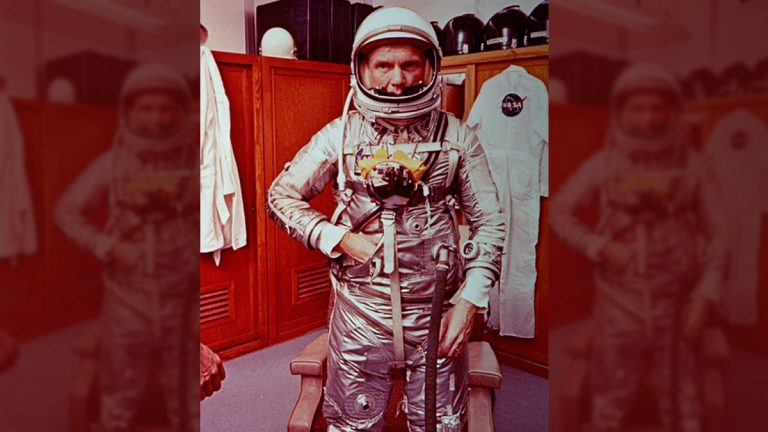 Astronaut John Glenn stands in his space suit