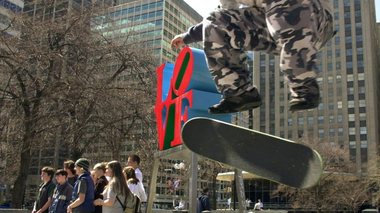 Mike Cole, 14, of Jenkintown, Pa., performs a kick-flip over a trash can in JFK Plaza, or 'Love Park' as it's known to skateboarders, while tourists pose for a photograph in Philadelphia.  (Douglas Bovitt/AP Photo, file)